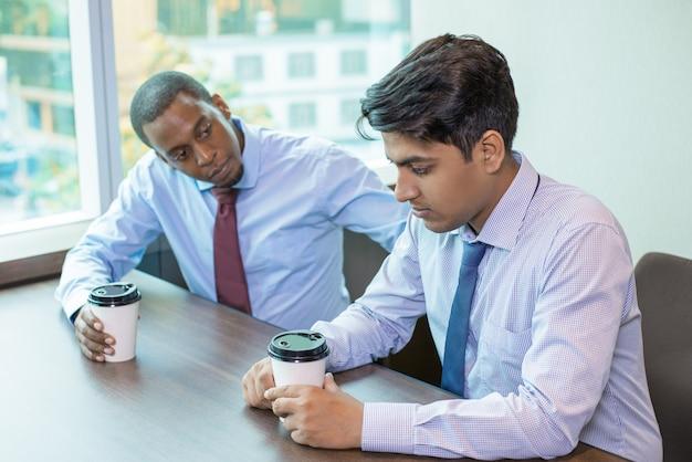 Upset coworkers drinking takeaway coffee