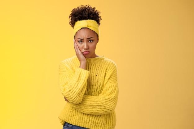 動揺してかわいい憂鬱な若い臆病な女の子は、悲しみを感じて後悔しているタッチ頬の痛みを伴う歯痛は動揺して悲惨なピットの表情を作り、不安定な黄色の背景に立っているのか不確かな問題を抱えています。