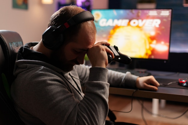 夜遅くに居間でゲーム机に座っているビデオゲームを失う動揺したサイバープレーヤー。ヘッドフォンとプロのジョイスティックを使用してオンラインチャンピオンシップのゲームをストリーミングする男