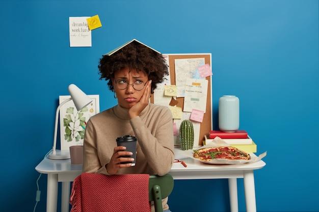 Upset dark skinned woman has notebook on head, keeps hand on cheek, holds takeaway coffee, feels tired and dissatisfied