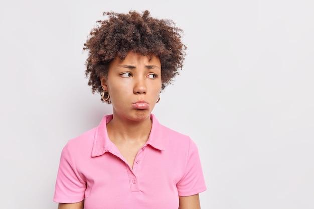 Расстроенная, удрученная кудрявая афроамериканка сжимает губы, грустно смотрит в сторону с несчастным выражением лица, одетая в повседневную розовую футболку, позирует на фоне белой стены