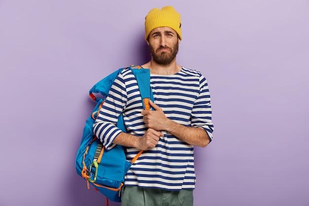 Autostoppista sconvolto e abbattuto posa con un grande zaino, vestito con un maglione da marinaio a strisce, stanco dopo un lungo viaggio