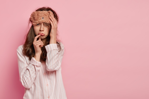 Upset dejected woman purses lower lip, wears sleepmask, dressed in comfortable pyjamas