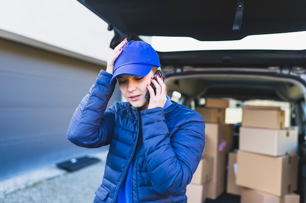 Upset delivery girl talking on phone