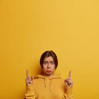 Upset depressed european woman waits for explanation, looks sadly , points fingers up, demonstrates something unpleasant upwards, purses lips, wears hoodie, models over yellow  wall