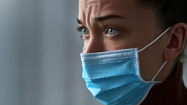 Расстроенная подавленная тоска грустно плачет женщина в защитной маске со слезами на глазах во время болезни