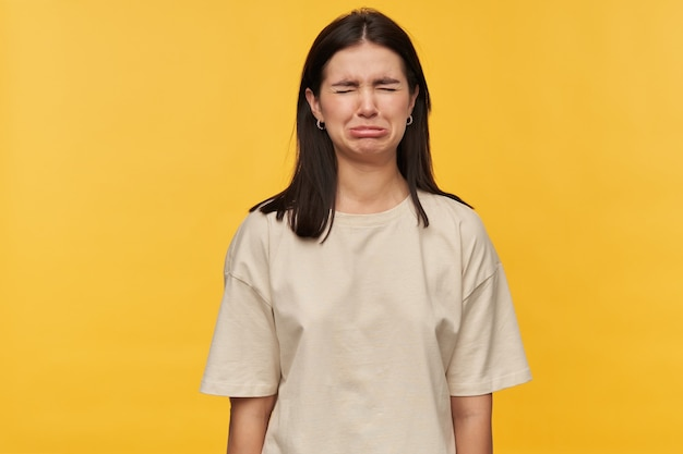 Upset depressed young woman with dark hair and eyes closed in white tshirt looks offened and crying over yellow wall