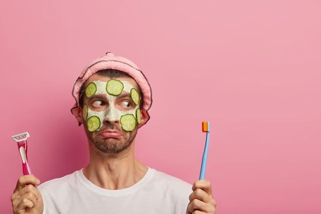 절망적 인 남자가 칫솔과 면도기를 들고 슬픈 표정을 지으며 오이로 점토 마스크를 착용합니다.