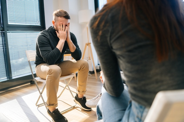 Upset desperate young man sharing problem sitting in circle during group interpersonal therapy session. sad depressed male talking with compassionate patients and psychotherapist.