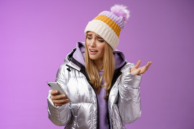 Upset disappointed attractive whining gloomy blond girl in silver jacket standing outside hat holding smartphone shrugging raising hand dismay complaining slow mobile internet, purple background.