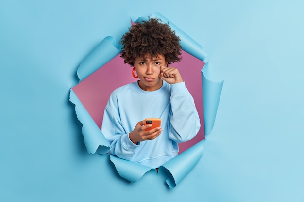 Upset disappointed curly woman wipes tears unhappy as boyfriend doesnt call her holds modern mobile phone in hands expresses negative emotions breaks through blue paper wall