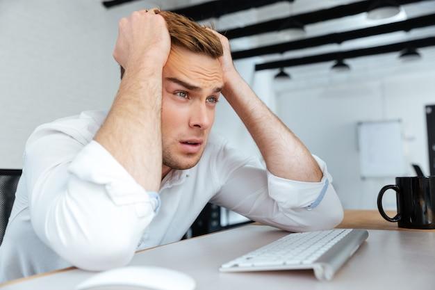 Расстроенный разочарованный молодой бизнесмен сидит на рабочем месте с руками за голову