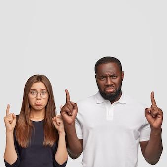 Donna e uomo sconvolti, insoddisfatti, portano le labbra insoddisfatte, puntano entrambi gli indici verso l'alto