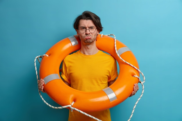 Upset displeased adult man carries ring lifesaver, wears transparent glasses and orange t shirt