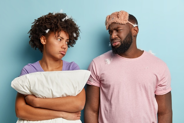 Upset displeased dark skinned husband and wife look with sad gloomy facial expressions at each other, have bad mood after sleeping for short time, wears sleepmask, isolated over blue wall.