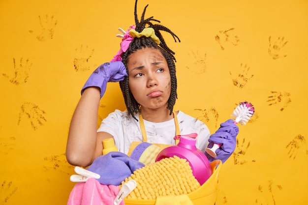 Upset displeased dark skinned woman busy doing laundry has frustrated look dirty face holds brush cleans toilet poses against yellow wall