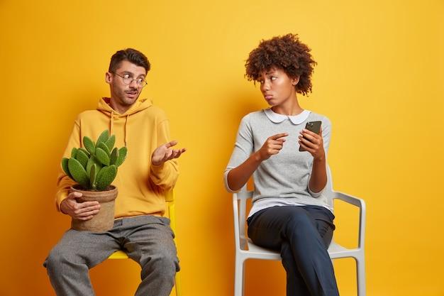Расстроенная недовольная этническая женщина показывает на смартфон, озадаченный мужчина пожимает плечами. межрасовая пара пытается решить проблему с помощью современного гаджета