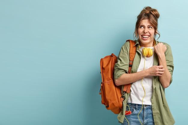 화가 난 여성은 손을 문지르고, 위쪽으로 보이며, 불만족스러워 웃는 얼굴을하고, 노란색 헤드폰을 착용합니다.