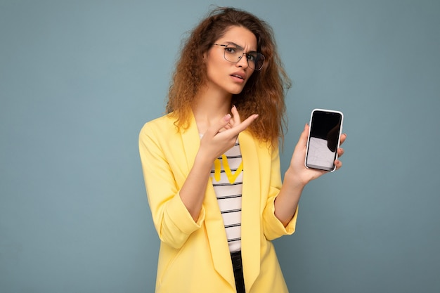 Upset dissatisfied attractive young woman with curly dark blond hair wearing yellow jacket and