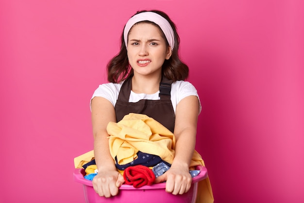 Upset dissatisfied brunette model poses isolated over pink