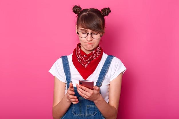 Расстроенная недовольная брюнетка милашка с пучками внимательно смотрит на экран своего смартфона, будучи занятой, с пучками на голове, стоя изолированными над розовым.