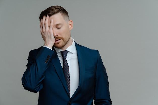 불만족스러운 사업주 또는 공식적인 마모를 입은 남성 직원이 얼굴에 손을 잡고 좌절감을 느끼고 회색 배경에 서있는 동안 나쁜 소식을받는 것에 대해 스트레스를받습니다. 실패 개념