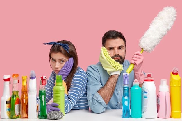 Upset dissatisfied woman and man sit back to each other, have gloomy expressions, tired after work about house, hold sponge, brush
