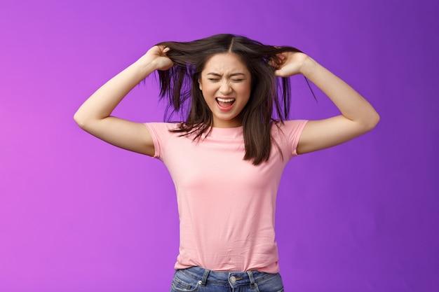 悲鳴を上げて眉をひそめている苦しめられたアジアのブルネットの女の子を動揺させ、貧弱なヘアケアにうんざりしている髪を抜く、失望の弱いストランド、イライラする紫色の背景に立ち、腹を立てて不平を言うヘアサロン。