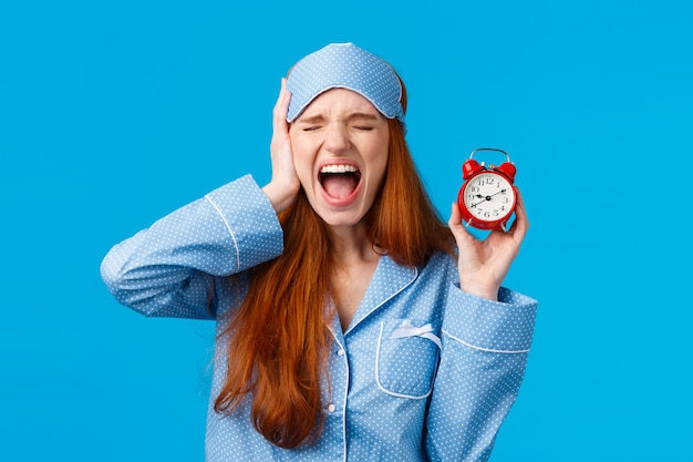 Upset and distressed screaming redhead lovely girl feeling bothered and depressed, holding red alarm clock and shouting with closed eyes and uneasy face, being late, hate wake-up early