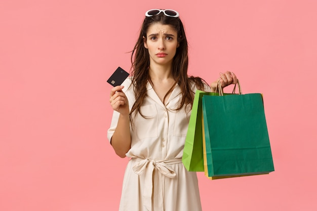 Upset and distressed young brunette female feeling sad spent all money, looking uneasy and concerned at credit card, holding shopping bags, standing pink wall gloomy