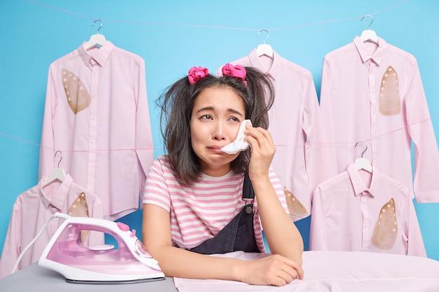 Расстроенная грустная азиатская девочка-подросток с двумя хвостиками вытирает слезы платком, опирается на гладильную доску, позирует возле выглаженной одежды на вешалках