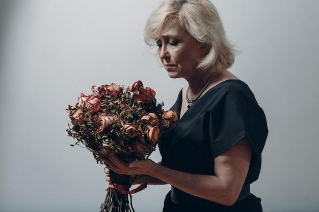 화가 난 할머니는 마른 오래된 장미 꽃다발을 들고 있습니다.
