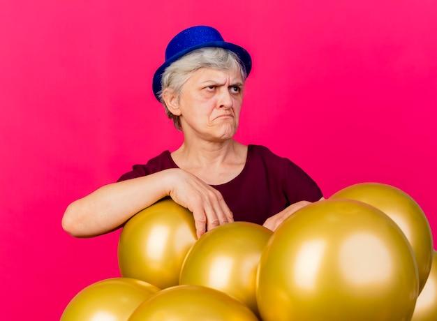 パーティーハットをかぶって動揺している年配の女性は、ピンクの側面を見ているヘリウム気球で立っています