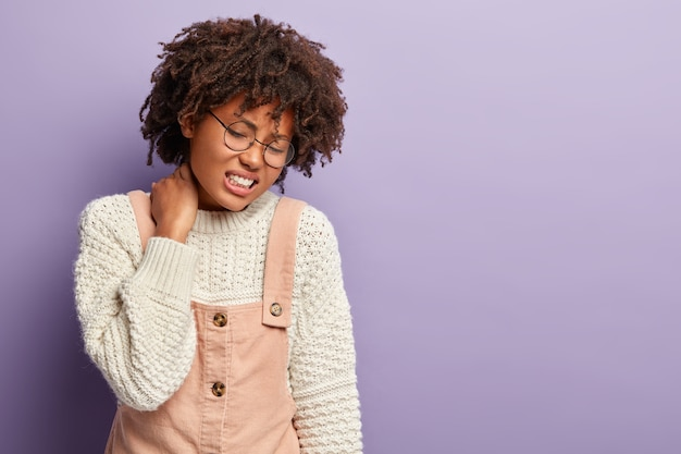 Upset ethnic woman feels terrible pain in neck after falling from stairs, grimaces from painful feelings, has problems with health and pain in spine, has sedentary lifestyle, isolated on purple