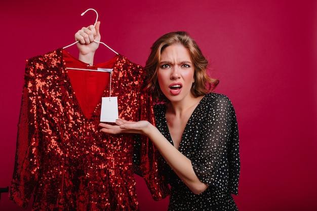 Расстроенная европейская девушка сердится на цены в магазине одежды