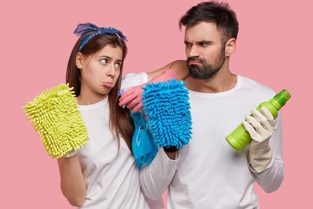 Расстроенные европейские женщина и мужчина хмурятся, глядя друг на друга, держат в руках спрей и бутылку моющего средства, разноцветные тряпки.