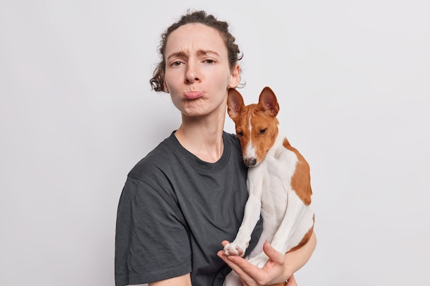 動揺している雌の動物愛好家は、バセンジー犬を手に持っていることに不満を感じています。彼女のペットは病気であるため、不幸に感じています。白で隔離された獣医の診察が必要です。
