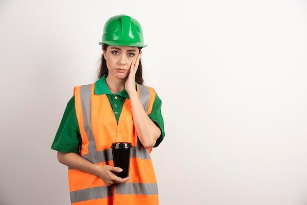 Costruttore femminile turbato che tiene tazza nera. foto di alta qualità