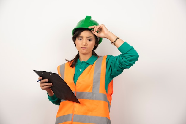 Sconvolto ingegnere industriale femminile in uniforme con appunti su sfondo bianco.