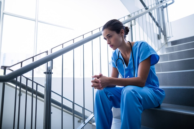 Upset female surgeon sitting on staircase