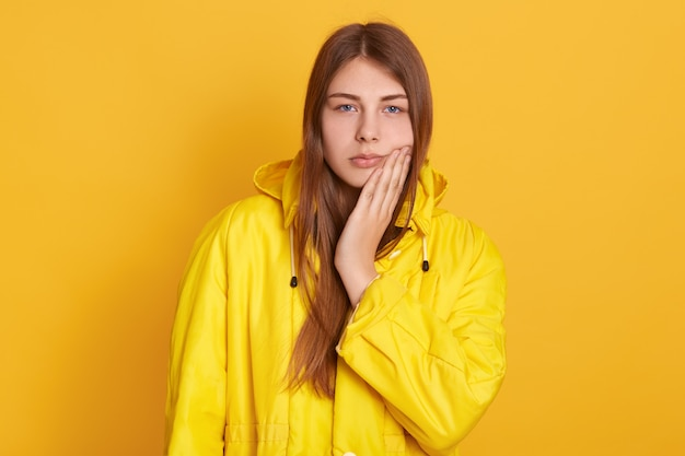 Upset female wearing yellow jacket touching her cheek, suffering from toothache, having medical problems, standing against yellow wall.