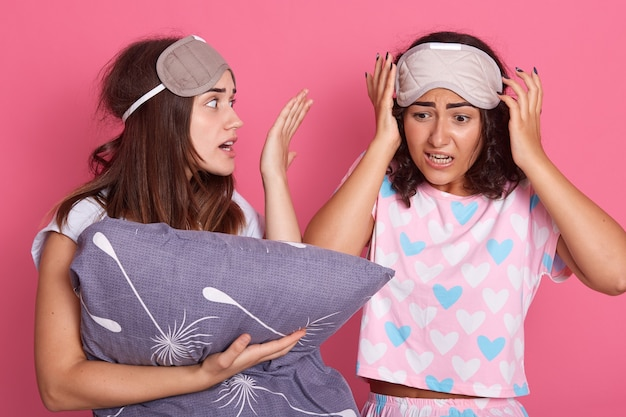 Upset friends girl in night suit for a pajama party on pink background
