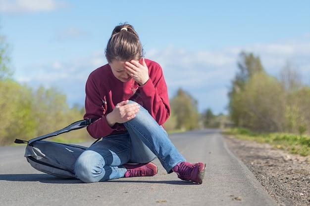 Расстроенная испуганная девушка упала на дорогу и заплакала от боли. женщина человек сидит на асфальте, получил травму.