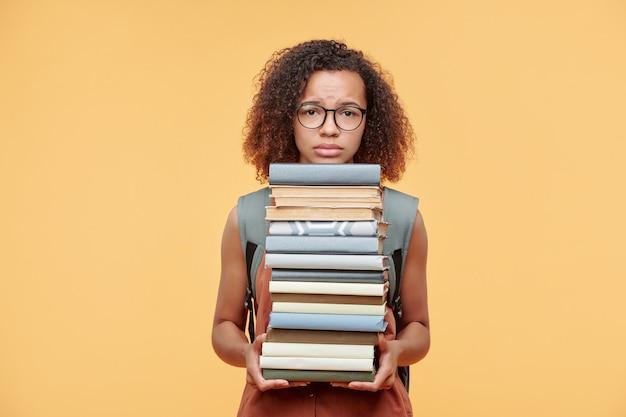 Расстроенная хмурящая афроамериканская девушка с вьющимися волосами держит стопку книг на желтом фоне, время готовиться к экзамену