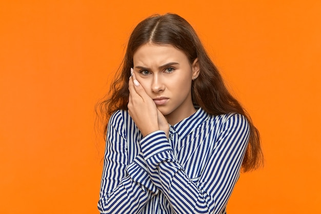Upset frowning young european woman in striped shirt holding hand on her cheek because of toothache.