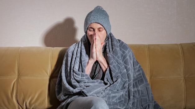Расстроенный замерзший мужчина в вязаной шапке с серым пледом дрожит от холода, сидя на современном диване в гостиной во время выключения отопления дома.
