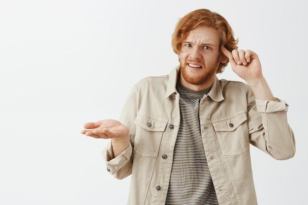 Tirante barbuto arrabbiato e frustrato di redhead che posa contro il muro bianco
