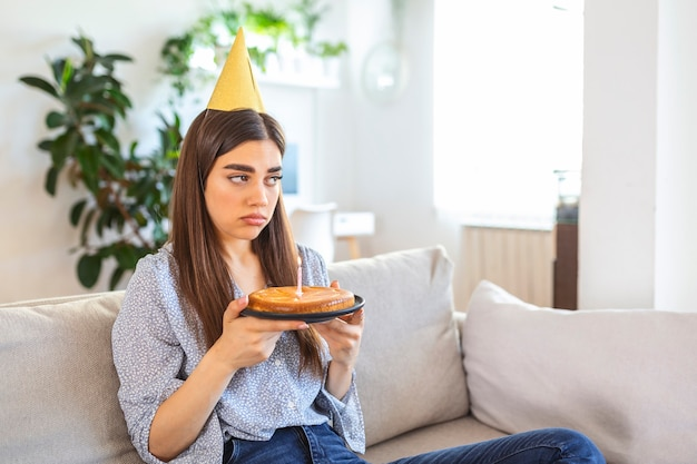 Upset and frustrated single woman in party hat celebrating birthday alone at home