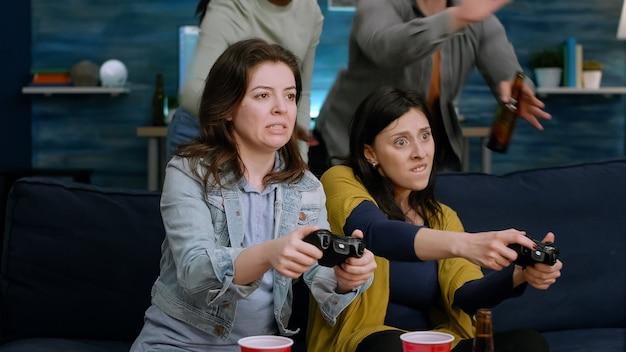 ゲームのジョイスティックを使用してオンラインビデオゲームの競争に負けているゲーマーを動揺させます。居間で夜遅くソファに座ってビールを飲みながら、社交を楽しんでいる多民族の友人のグループ