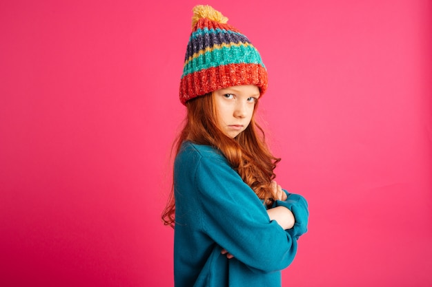 Upset ginger girl looking camera and and holding hands folded isolated